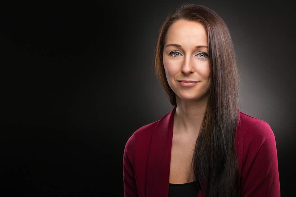 Bewerbungsfoto einer Frau mit Blazer und dunklem Hintergrund